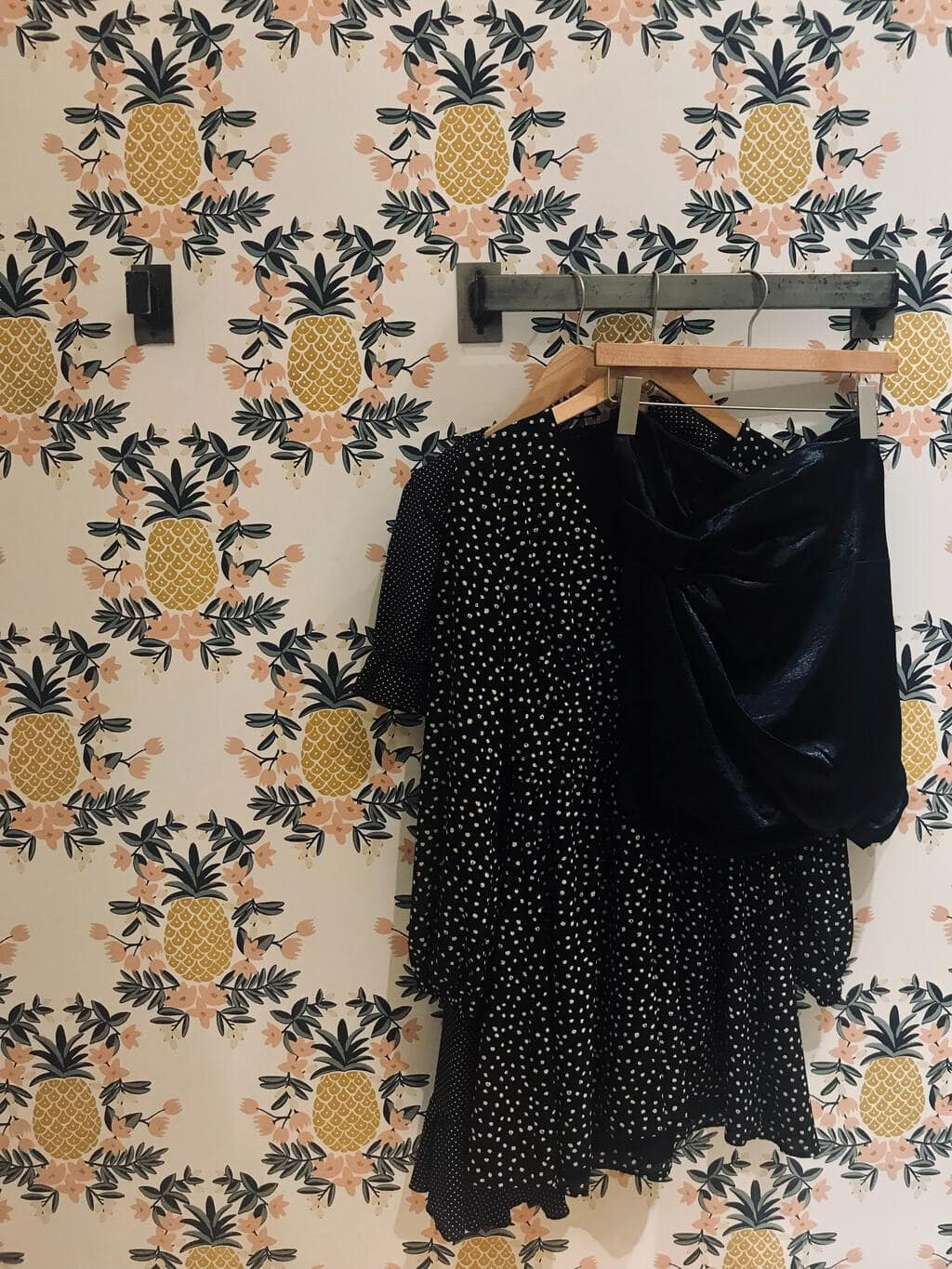 dresses and skirt hanging in front of pineapple wallpaper