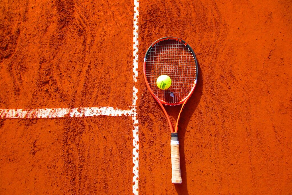 Tennis racquet and ball on orange tennis court.