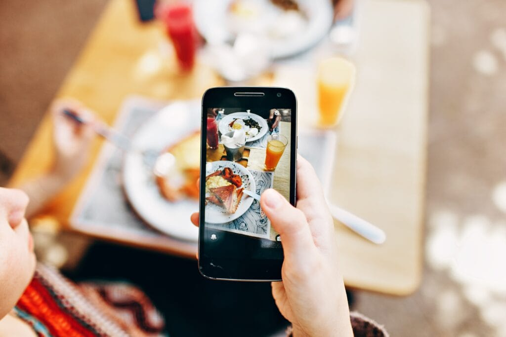 Person taking a picture of a brunch meal.