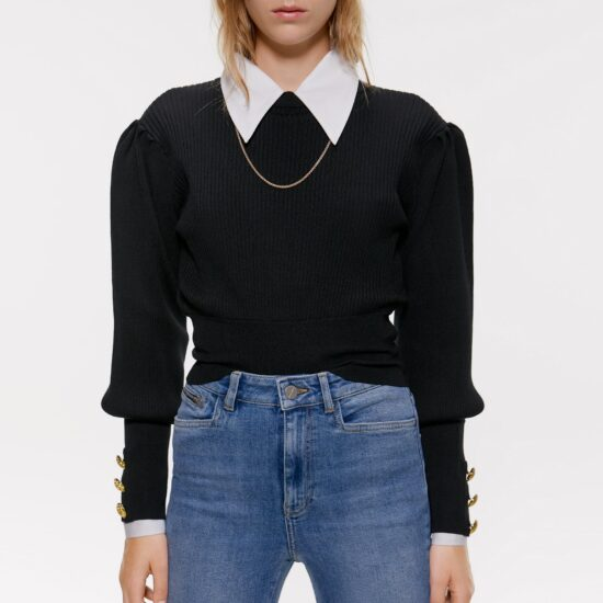 Young woman wearing a black puff-sleeve sweater with three gold buttons at each cuff over a white shirt with an oversized collar, as well as a skinny gold chain necklace and light-wash skinny jeans