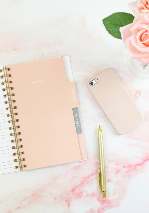 Flat lay on light pink marble surface featuring planner, gold-colored pen, iPhone in pale pink case, and pale pink roses