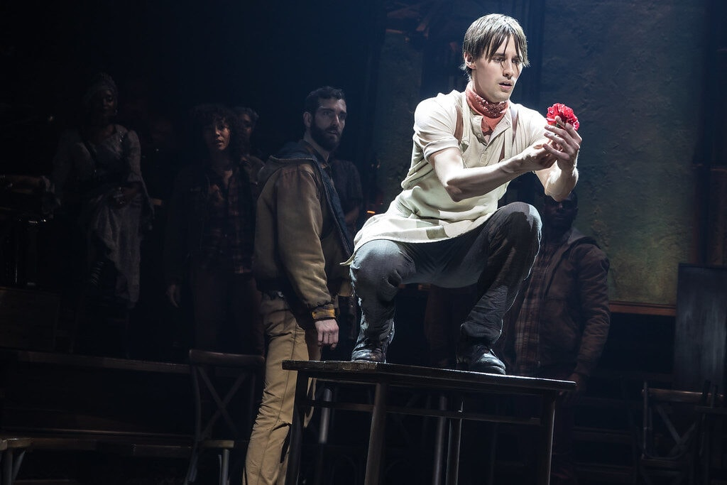 Promotional photo of Orpheus holding a flower - hadestown costumes and hadestown fashion guide