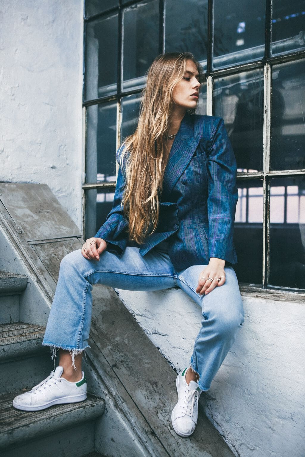 Woman with very long blond hair sitting on a window ledge outside next to stairs, looking away from the camera and wearing a blue plaid double-breasted blazer, loose-fitting light-wash jeans with distressed hems, and Adidas sneakers