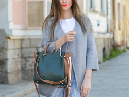 Young woman with long straight hair and very bright pink lipstick standing on a cobblestone road, wearing a light gray jacket over a white t-shirt and light blue pinstripe pants, and carrying a leather top-handle bag in the crook of her arm