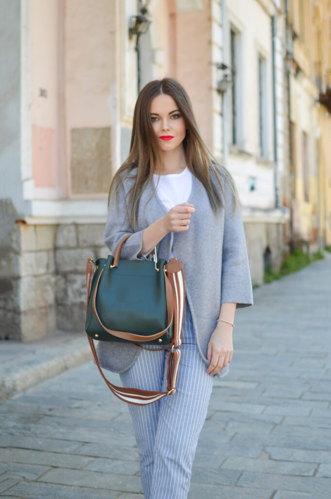 Fall transition outfits: Young woman with long straight hair and very bright pink lipstick standing on a cobblestone road, wearing a light gray jacket over a white t-shirt and light blue pinstripe pants, and carrying a leather top-handle bag in the crook of her arm