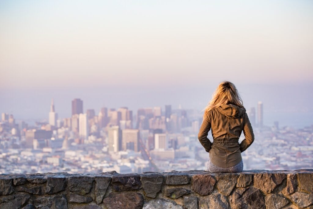 Young woman sitting, looking at city skyline.