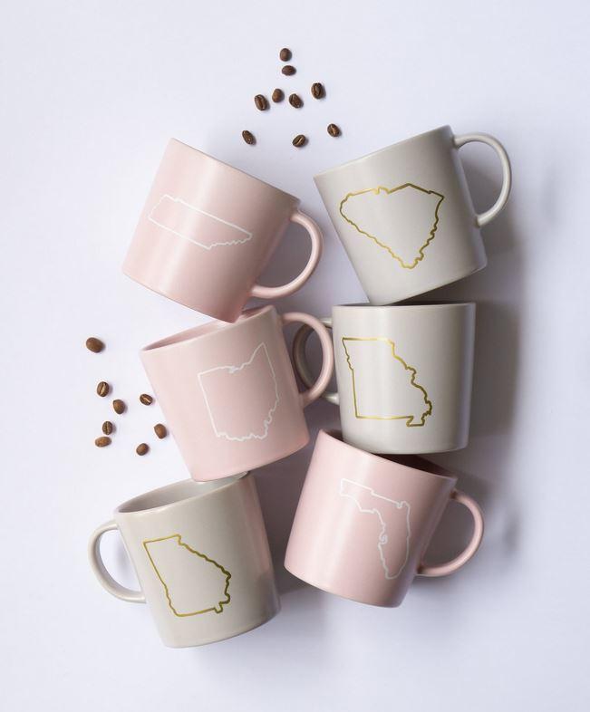 Pastel pink + grey state mugs.