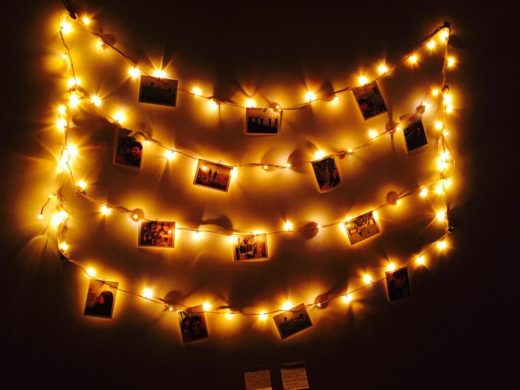 Photos + fairy lights on a dorm wall.