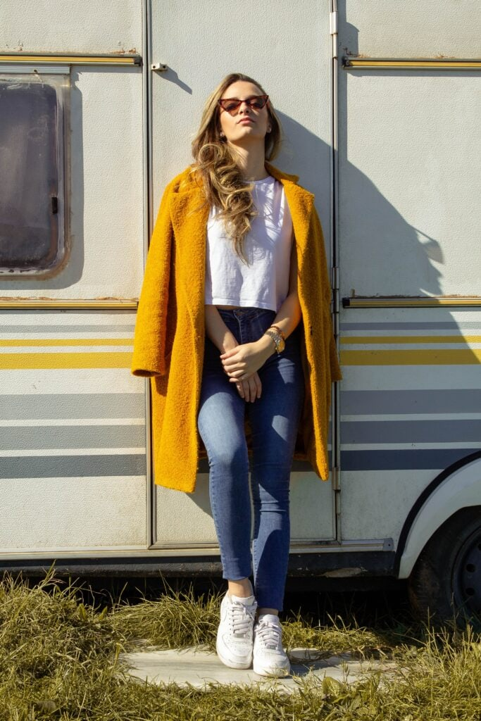 Woman standing outside in front of vehicle wearing yellow coat over white boxy-fit t-shirt and skinny jeans, as well as a watch and a bracelet, earrings, cat-eye sunglasses, and white sneakers