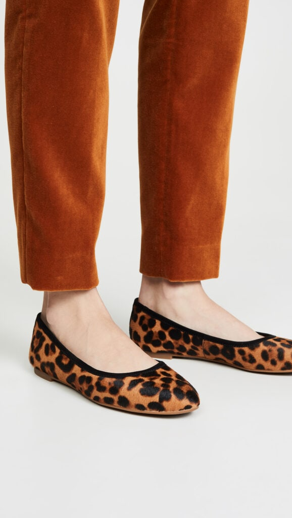 Shot of model's legs from the shins down; model is wearing dark, warm beige slim-fitting pants and calf-hair leopard-print ballet flats with black trim