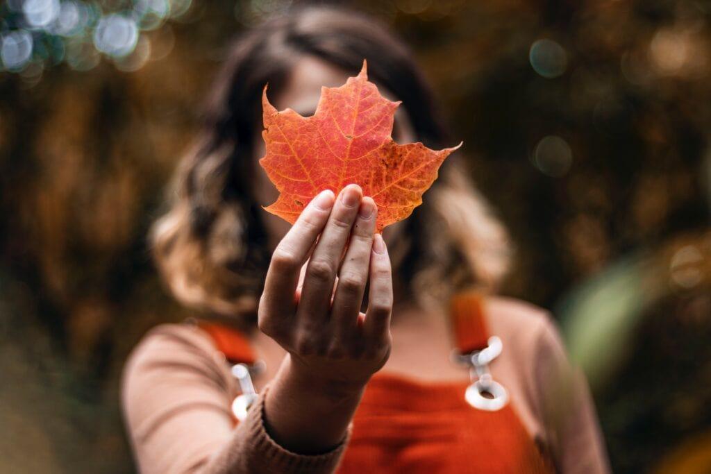 Girl holding autumn leaf.