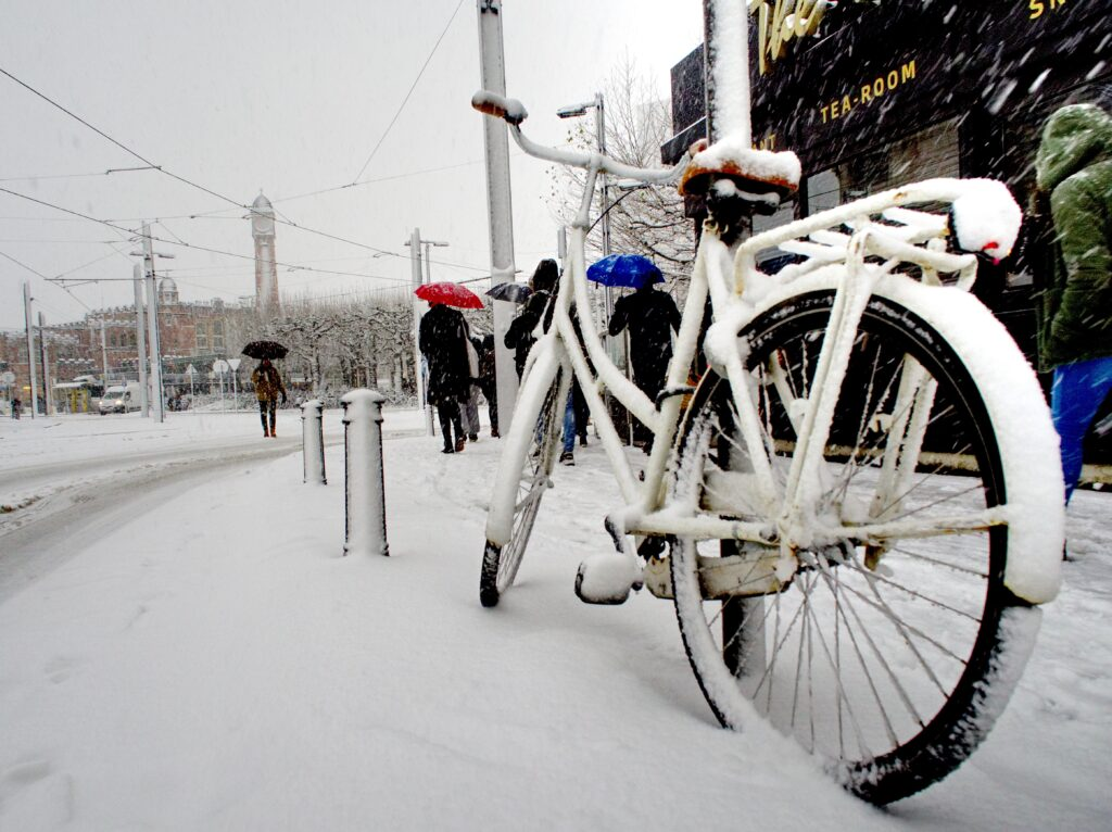 Bikes covered in snow in city.