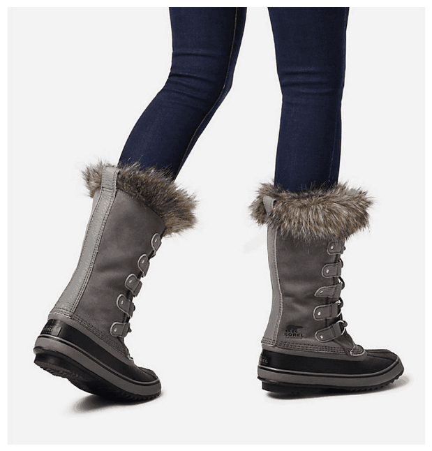 Cute snow boots guide: Three-quarter view from behind of woman's legs in dark-wash blue skinny jeans and gray and black Sorel Joan of Arctic™ boots