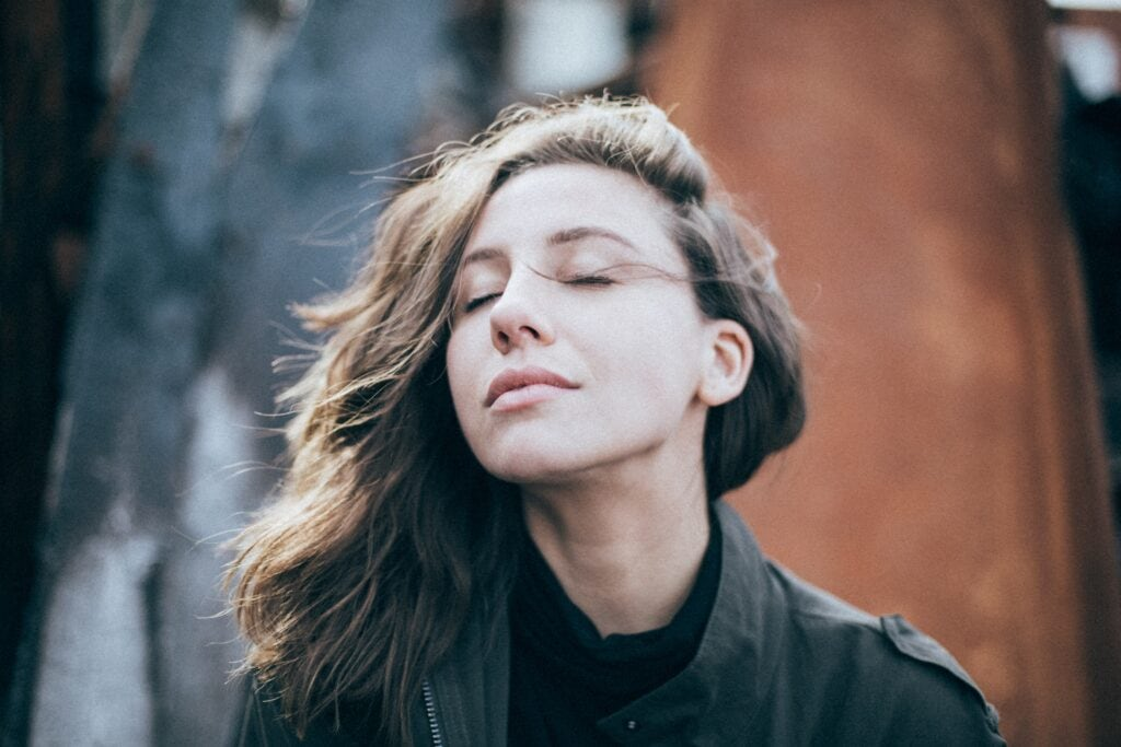 Woman with eyes closed and wind blowing her hair