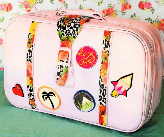 pink suitcase with patches and fabric