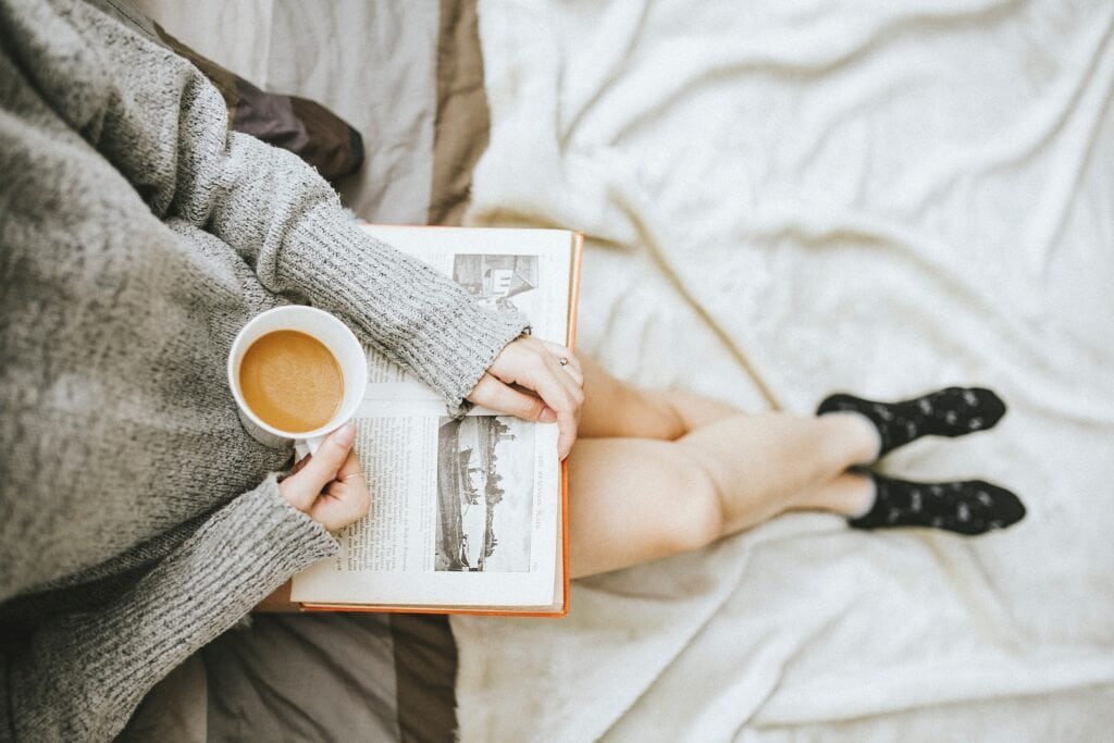 Woman holding book and coffee