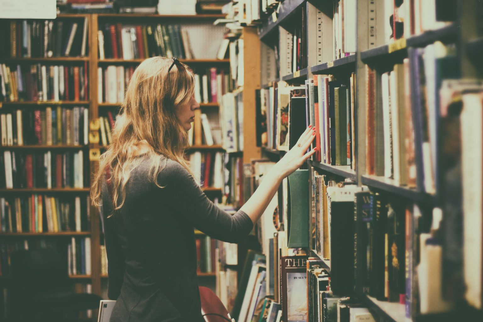 Stock photo of a girl looking through books