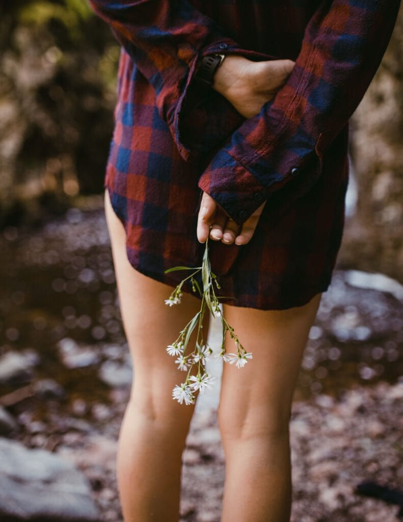 Girl wearing a flannel holding a flower behind her back.