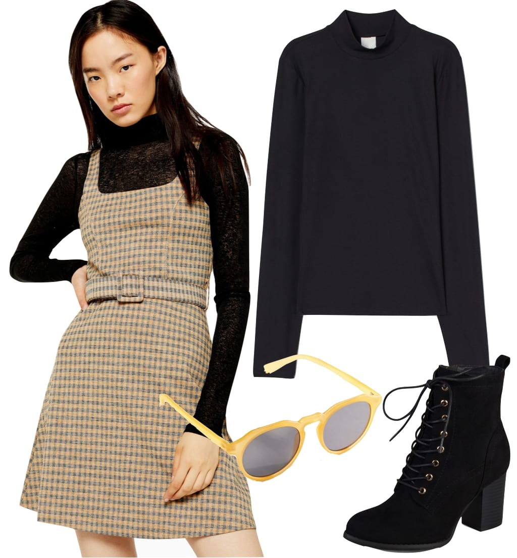 Emma Roberts style 2019: Outfit #1: checked belted pinafore mini dress, black turtleneck top, black lace-up booties, and mustard round plastic sunglasses