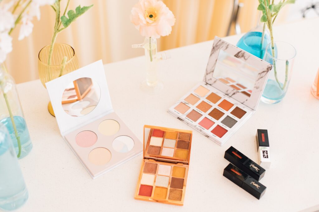 Decluttering tips - get rid of old makeup. Photo of makeup palettes on white table