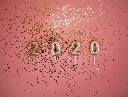 2020 pale gold number candles and gold sparkles against a coral-pink background