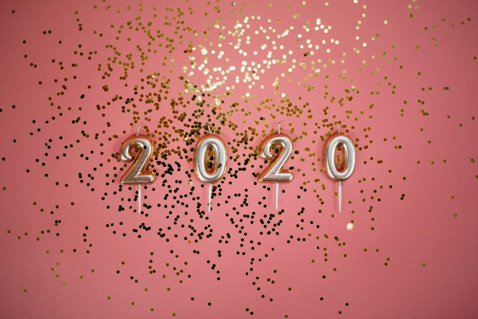 2020 pale gold number candles and gold sparkles against a coral-pink background old fashion trends coming back
