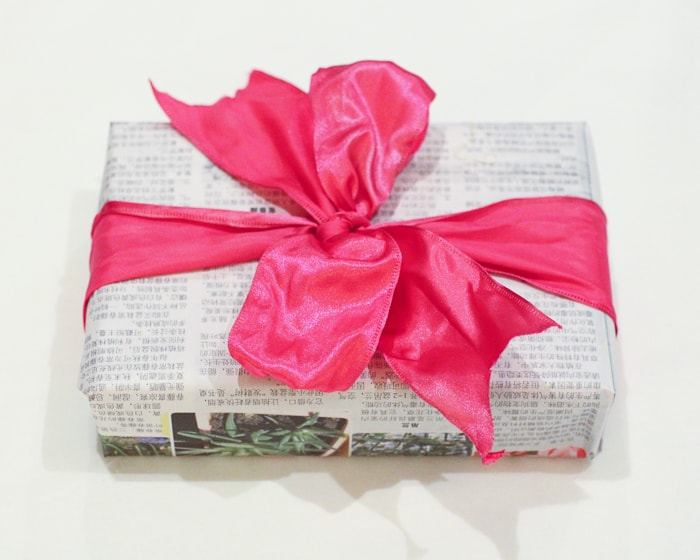 Gift wrapping ideas - newspaper wrapped present with pink bow.