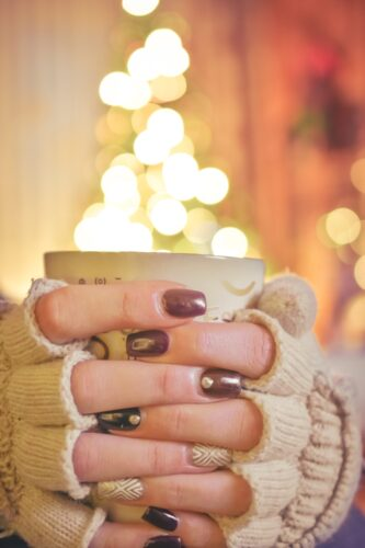 Stock photo of someone holding a mug with painted nails