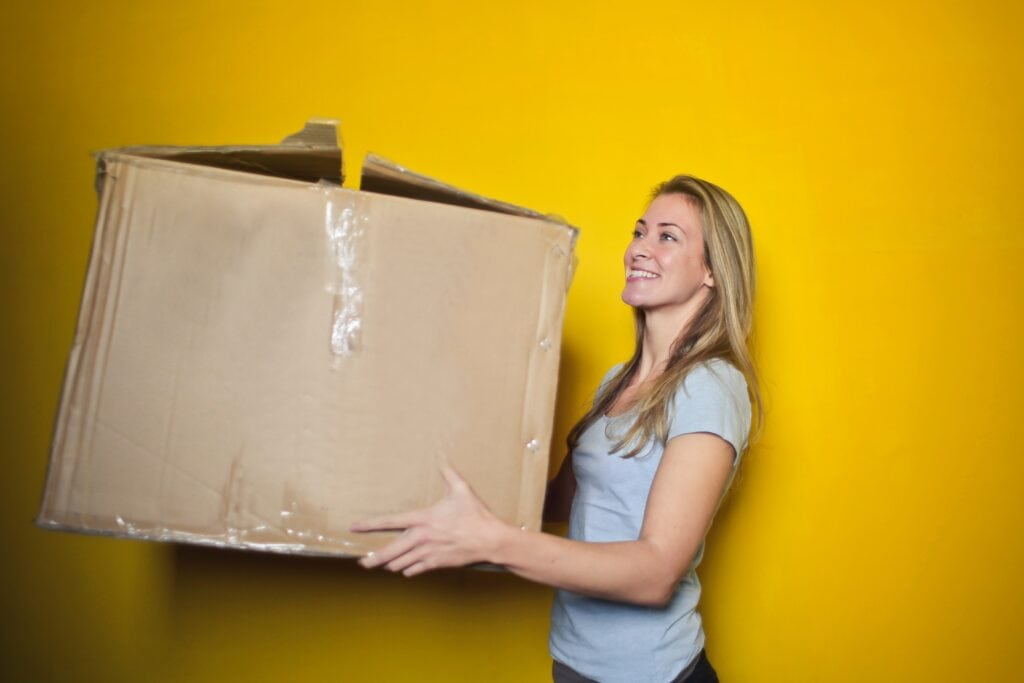 Decluttering tips - four box method woman holding box