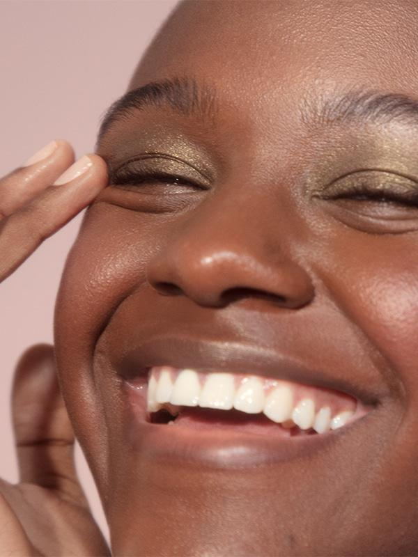Close-up shot of woman smiling against pale pink background and wearing Glossier Lidstar in