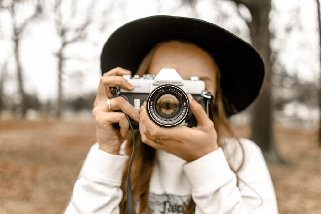 girl holding camera over face