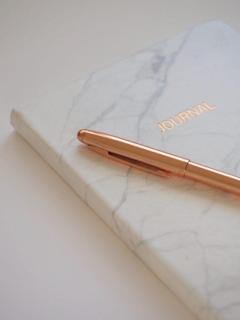 gold pen on white journal