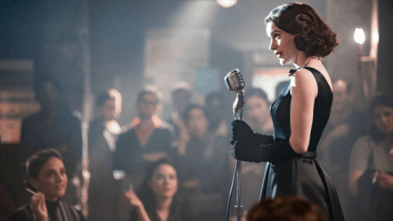 Mrs Maisel fashion: Photo of Midge Maisel from The Marvelous Mrs Maisel wearing a black dress and gloves while performing