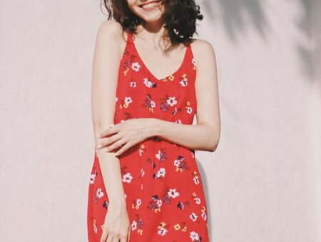 Smiling young woman wearing sleeveless red floral-print dress standing against white wall outside