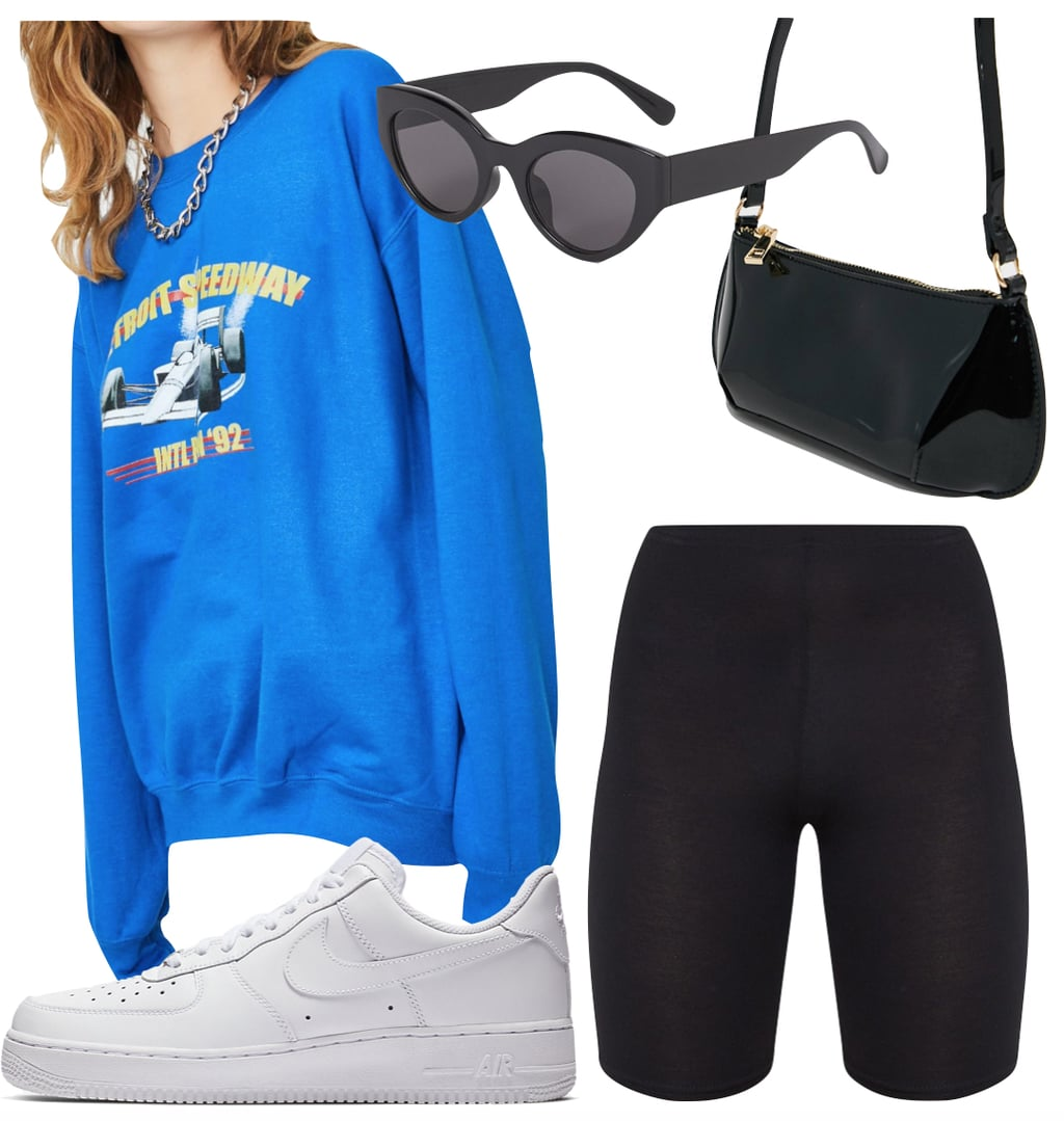 Madison Beer Outfit #2: royal blue graphic print crewneck sweatshirt, black biker shorts, black sunglasses, black patent shoulder bag, and white low top Nike Air Force 1 sneakers