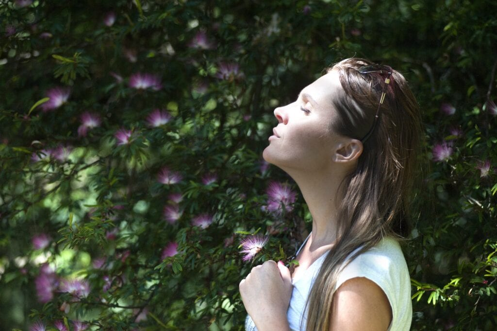 Woman facing sun with eyes closed surrounded by flowers