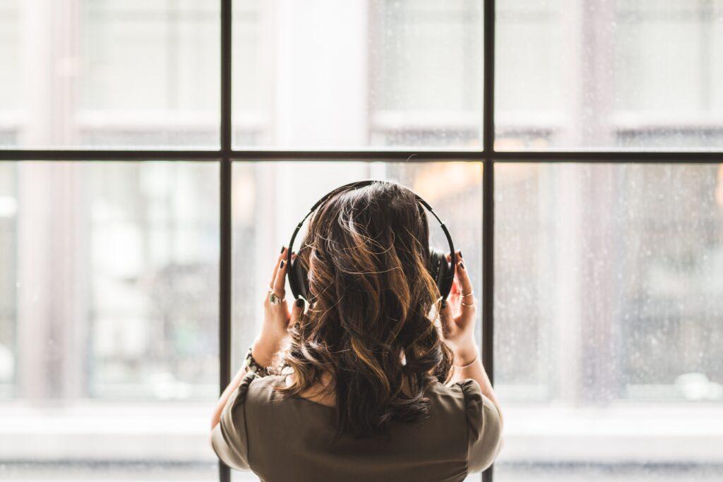 Woman listening to music through headphones.