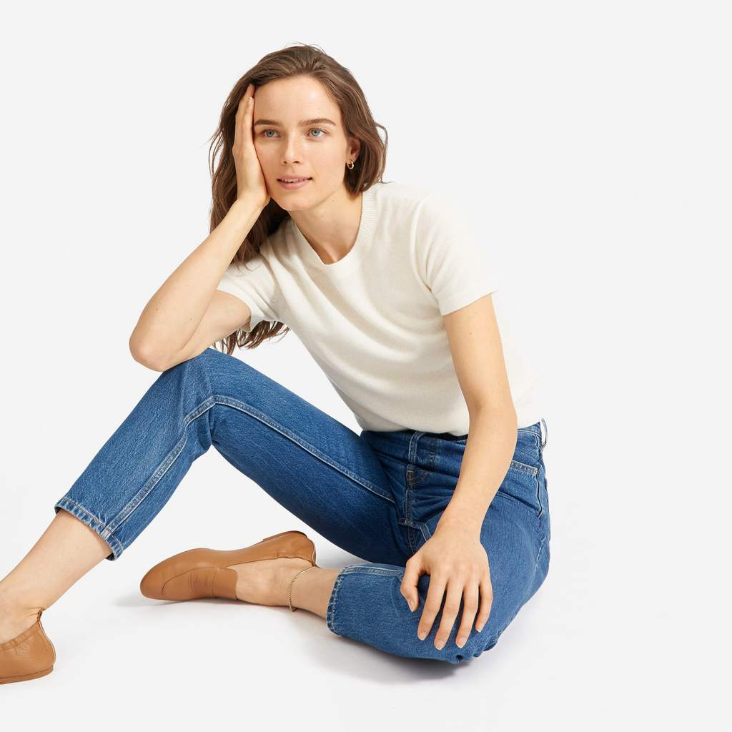 Woman sitting on the ground with her head in her hand wearing an ivory-colored short-sleeved sweater, cropped medium-wash jeans, and cognac-brown loafers
