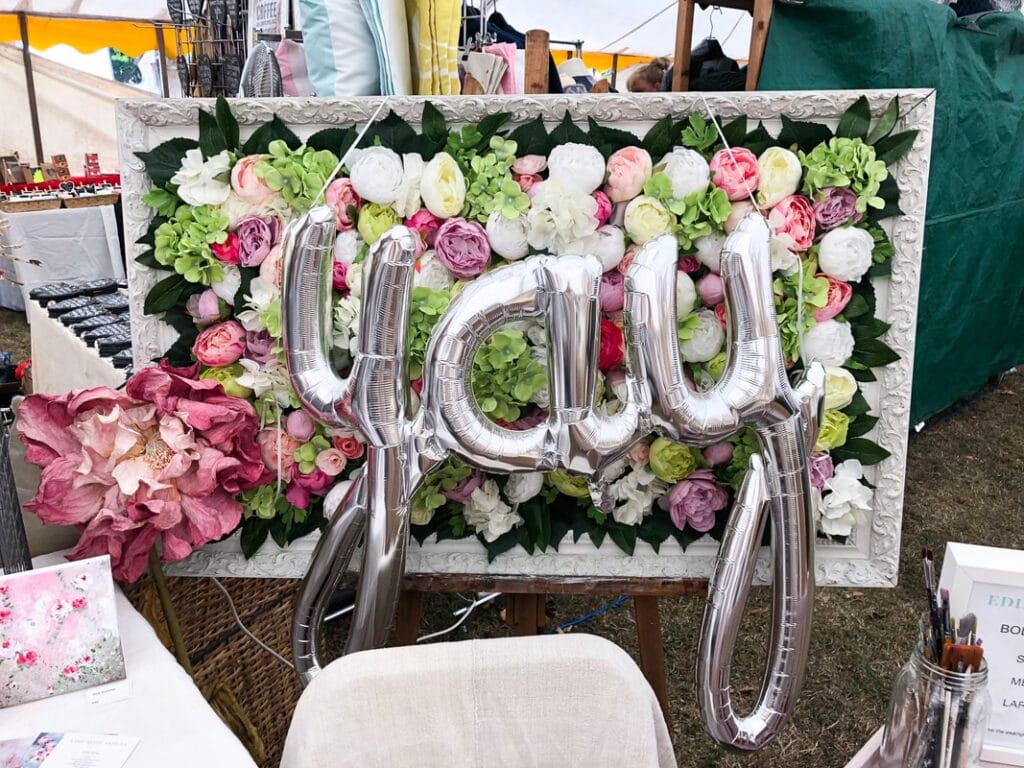 Spring DIYs: frame full of flowers behind yay metallic balloons