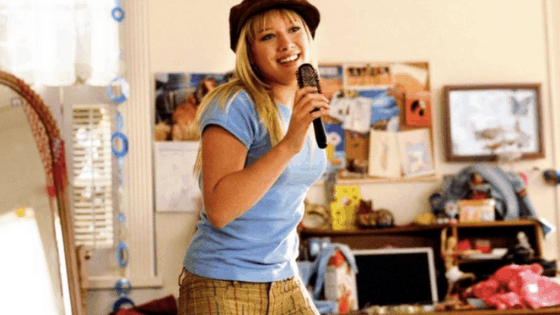 Still from the Lizzie McGuire movie, singing into her hairbrush.