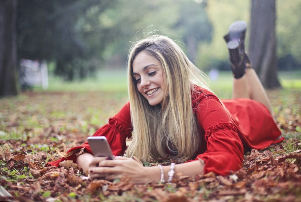 Woman smiling and texting on phone.