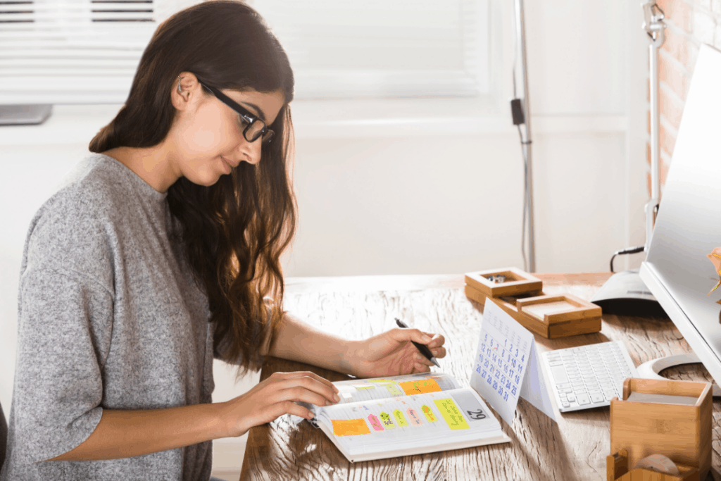 Woman writing out a schedule for her online classes