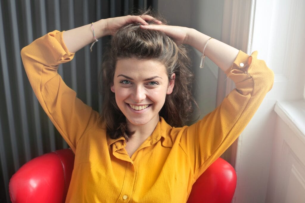 Woman in yellow shirt styling hair.