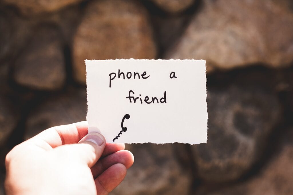 person holding note that reads phone a friend.