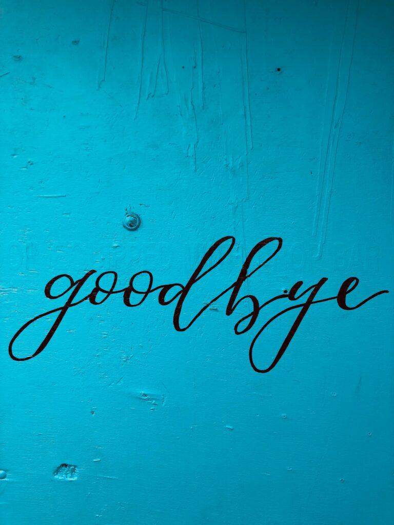 cursive goodbye painted on blue background
