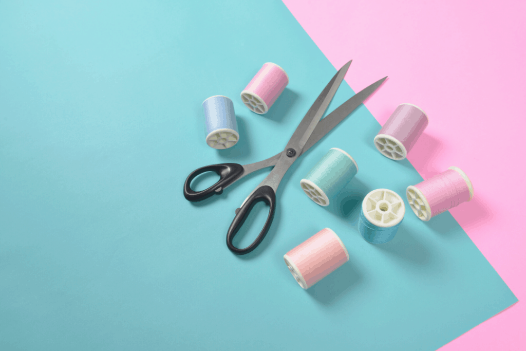 Photo of a sewing kit on a pink and blue background