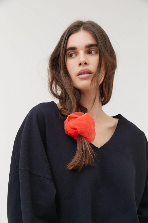 Girl in black shirt and coral orange scrunchie.