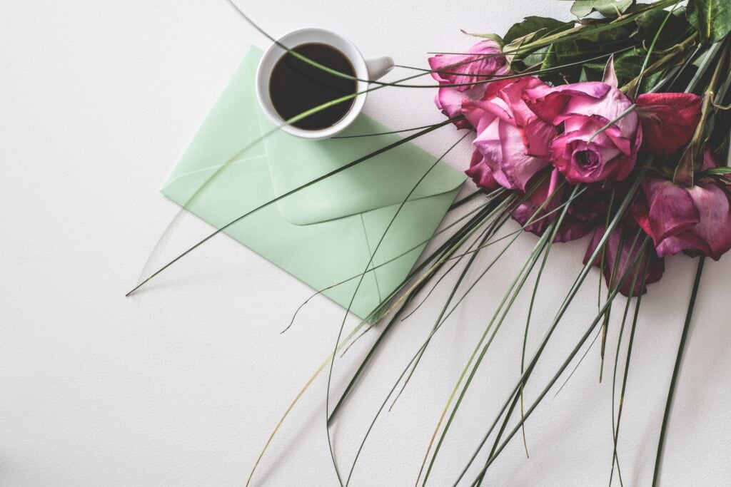 Coffee, flowers, and envelope.