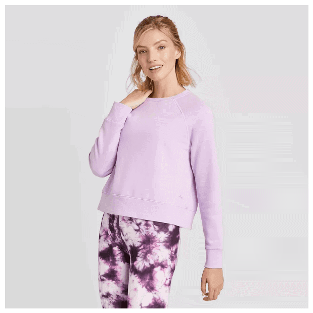 Model wearing JoyLab™ Crew Neck Long Sleeve Fleece in Pale Orchid and purple tie dye leggings, standing against light gray background