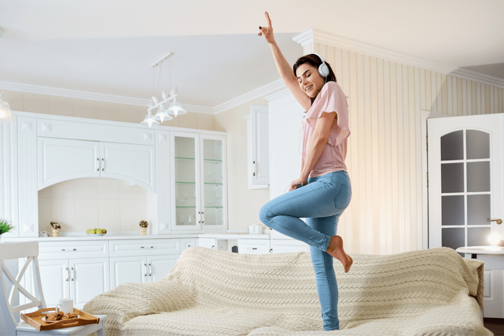 Photo of a woman dancing on her couch at home while wearing headphones